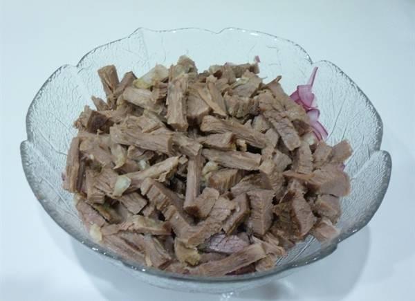 Заранее отваренную и охлажденную говядину нарезаем на бруски и выкладываем в миску к луку.