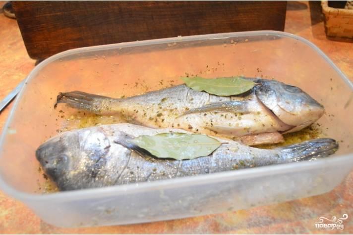 1.Первым делом тщательно чистим и моем рыбку, вытираем насухо. В миске смешиваем сок лаймов, оливковое масло и специи. На рыбе делаем неглубокие надрезы по всей длине и перекладываем ее в контейнер с крышкой, поливаем маринадом и добавляем лавровый лист (2 снаружи и по одному кладем внутрь). Отправляем рыбу в холодильник минимум на 30 минут.