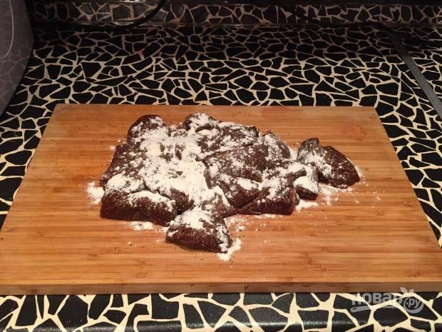 Печень промойте и обсушите. Затем нарежьте её кусочками, посолите и поперчите, а в конце обваляйте в муке.