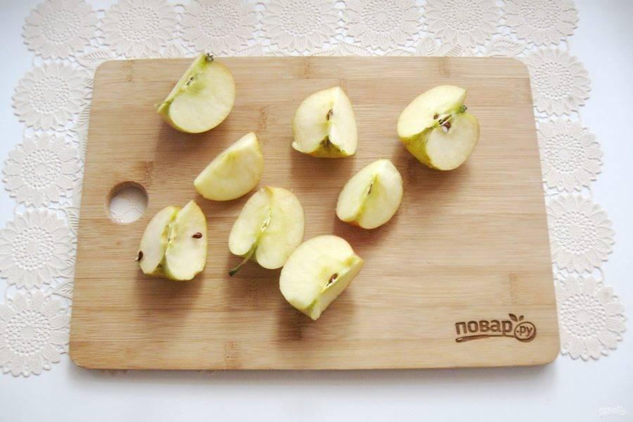 Яблоки помойте и разрежьте на четыре части.