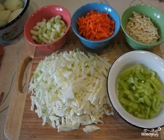 1. Помойте, почистите и нарежьте овощи таким образом: перец болгарский и капусту – полосками; черешки сельдерея – некрупными ломтиками; корень сельдерея и морковь – соломкой; помидоры – небольшими кубиками.