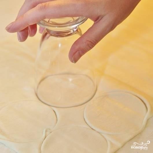 Раскатываем слоеное тесто до толщины примерно в 2 мм, вырезаем из теста круги диаметром примерно в 8 см.