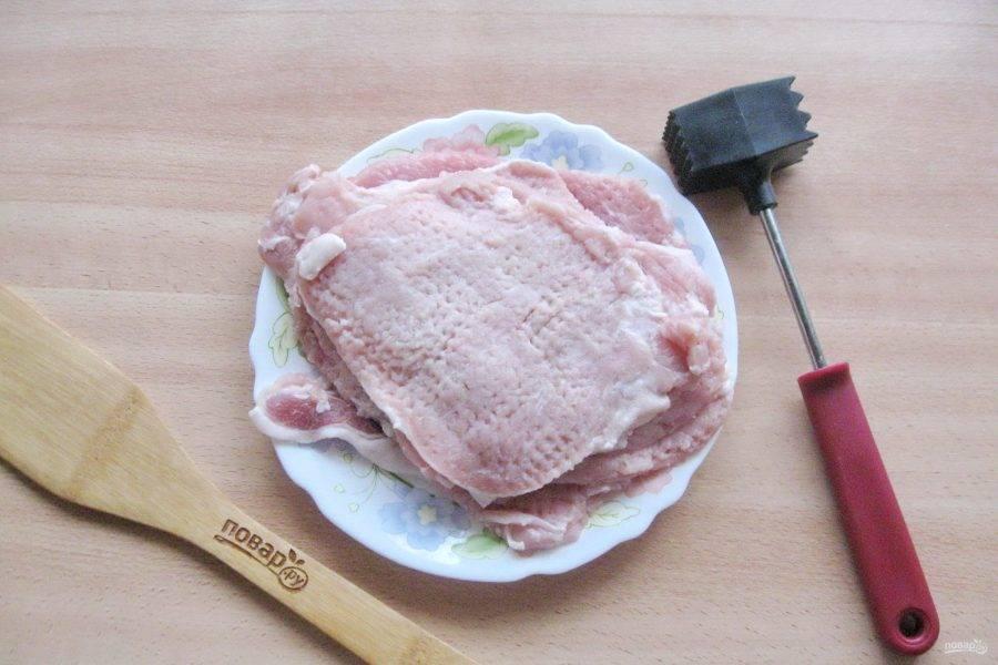 Свиную корейку помойте, высушите салфеткой и нарежьте слайсами. Затем каждый слайс отбейте с обеих сторон.