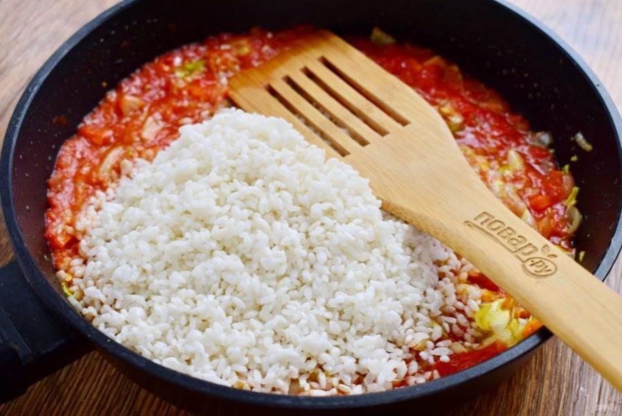 Рис промойте в холодной воде, откиньте на дуршлаг. Добавьте рис к тушеным овощам, перемешайте и готовьте в течение 1 минуты. Рис пропитается маслом, томатом соком и специями.