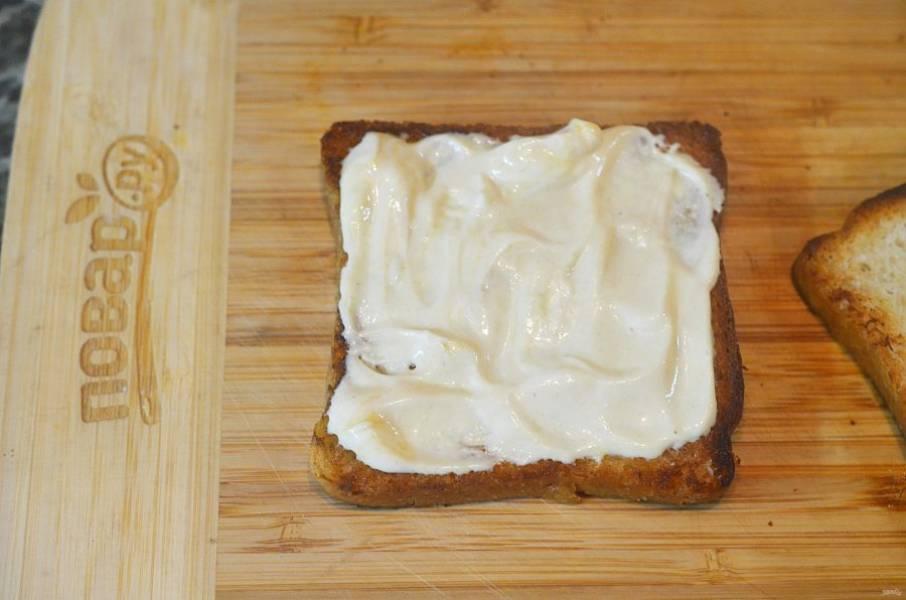 Смажьте один тост смесью горчицы и майонеза.