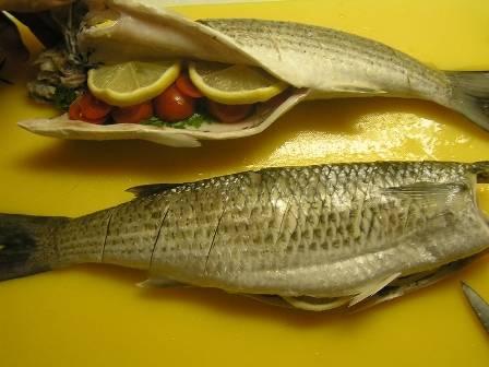 Нарезаем зелень, лимон разрезаем на тонкие кружочки. Если вы решили запекать рыбку с чесноком, чеснок чистим, измельчаем. В брюшко каждой рыбки вкладываем лимон, чеснок и зелень петрушки.