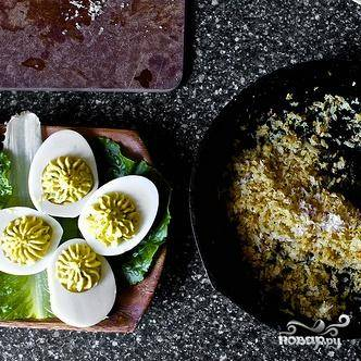 5. Посыпать яйца смесью панировочных сухарей, украсить оставшейся нарезанной зеленью петрушки и подавать на стол.
