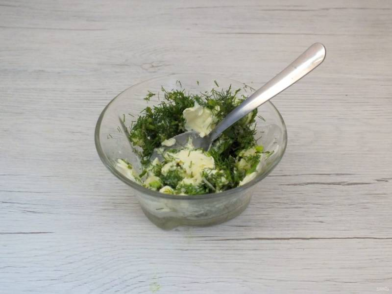 Пока готовится картошка, сделайте ароматную заправку. Сливочное масло натрите на терке, добавьте измельченные три зубчика чеснок и нарезанную зелень. Посолите и перемешайте.
