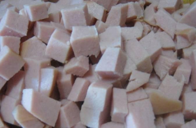 Вареную колбасу порежьте кубиком.