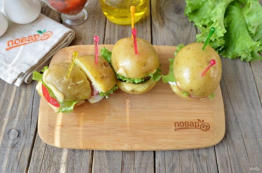 И сборка сэндвича. Для этого накройте половинками картофеля, вставьте шпажки или зубочистки, разрежьте на две части каждый сэндвич. Вот и все! Подавайте к столу!