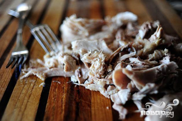 2. Достать курицу из кастрюли. С помощью двух вилок отделить мяса от костей. Слегка измельчить мясо. Вернуть кости в кастрюлю и продолжать варить под крышкой в течение 45 минут. Убрать кости из бульона.
