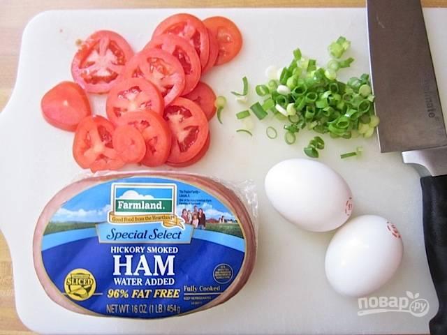 4.Помойте и нарежьте помидор кольцами, промойте зеленый лук и порежьте. Нарежьте тонкими кусочками ветчину, натрите сыр на средней терке.