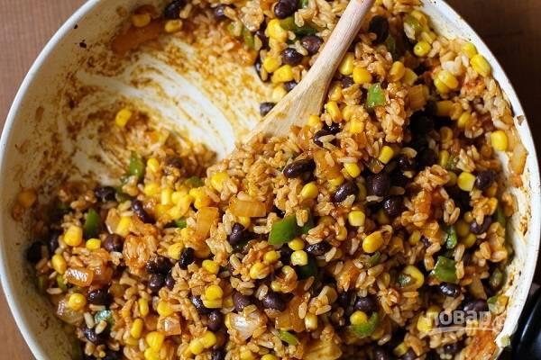 2. На сковороде разогрейте растительное масло. Обжарьте пару минут измельченный лук. После добавьте чеснок и острый перец. Выложите рис, половину соуса, кукурузу и фасоль. Посолите по вкусу. Через пару минут снимите начинку с огня.