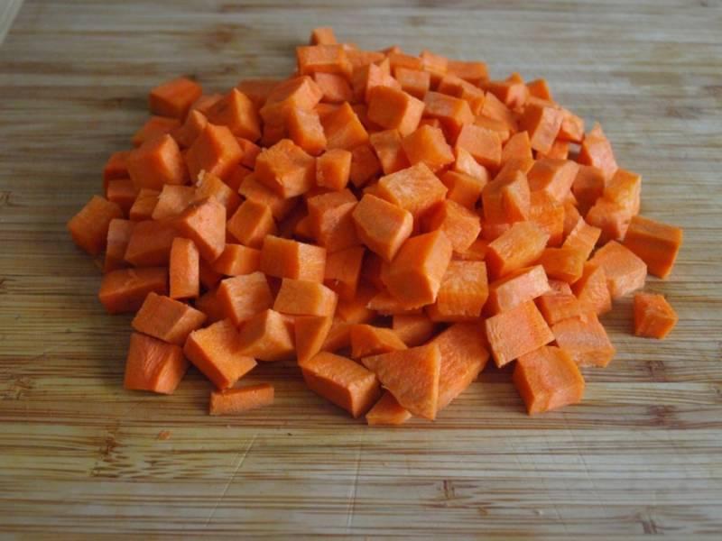 Тем временем очищаем и режем кубиками морковь.