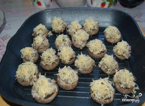 5.Шляпки грибов вытащить из духовки и начинить их приготовленной начинкой. Обсыпать сверху оставшимся сыром. Поставить шляпки с начинкой обратно в духовку и запекать, пока сыр не расплавится, и запечется в виде румяной корочки.