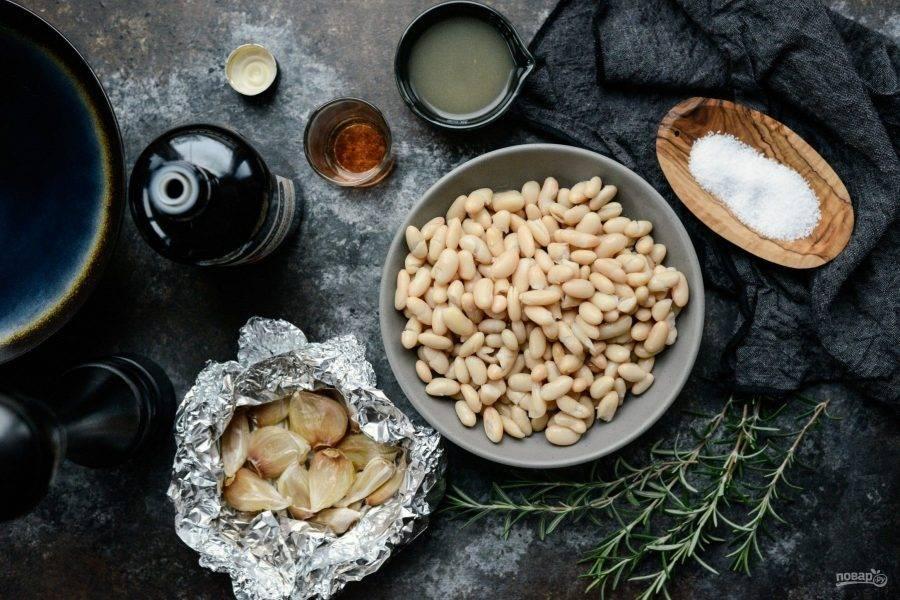 1. Заранее чеснок заверните в фольгу и отправьте в духовку. Запекайте его в течение 25 минут при 200 градусах. В это время слейте воду из банки с фасолью.