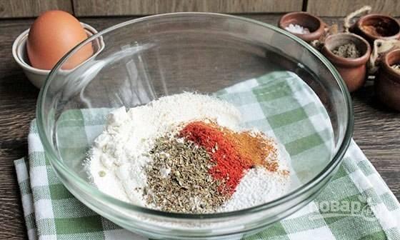 Пока приготовьте кляр. В миске перемешайте муку с солью, крахмалом, травами и специями для курицы.