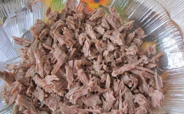 2. Теперь мясо мелко режем и выкладываем на дно салатницы. Можно немного посолить. Затем - слой лука, отжатого от маринада. Сверху - майонез.