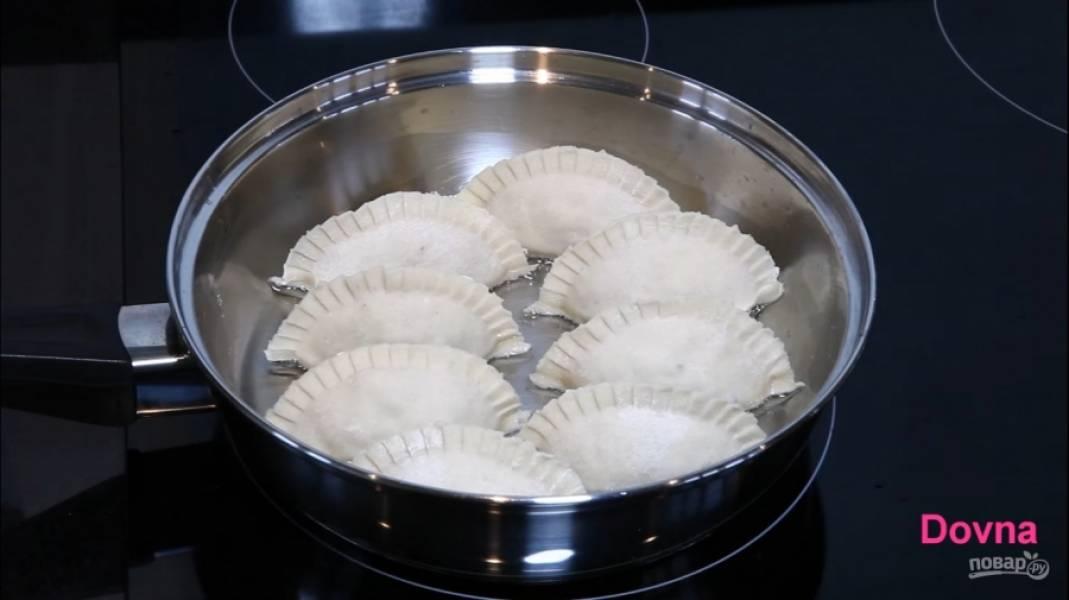 """5.Разогрейте на сковороде немного подсолнечного масла, обжарьте пельмени с одной стороны. Влейте в сковороду немного холодной воды, накройте крышкой и дайте пельменям немного """"попариться""""."""
