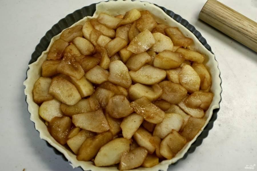 Яблоки порежьте на кусочки, кожуру лучше очистить. Протушите яблоки с сахаром и корицей, добавьте немного воды. Потом выложите яблоки сверху на печенье. Печенье впитает сок яблочный по время выпечки и не даст тесту размокнуть.