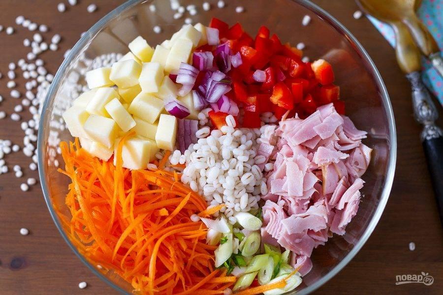 1.Крупу промываю и помещаю в воду, отвариваю и остужаю. Морковь очищаю и измельчаю на крупной терке, красный лук нарезаю кубиками, шалот измельчаю, красный перец и сыр нарезаю кубиками. Ломтики ветчины нарезаю кусочками. Выкладываю все подготовленные продукты в миску.