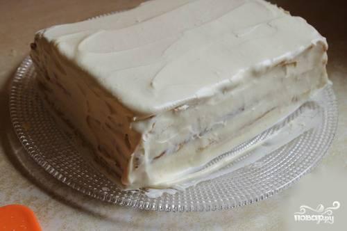 Один корж убираем в сторону. Он нам позже понадобится для украшения. Обмазываем торт со всех сторон: по бокам, верхушку, крема не жалеем.