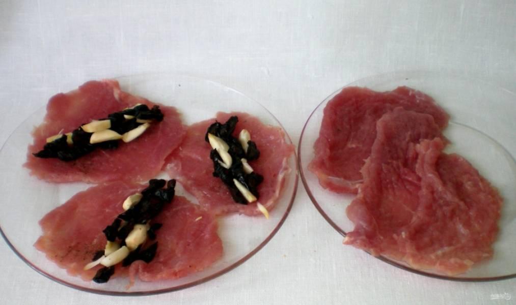 2. Свинину мою и нарезаю кусочками, затем отбиваю молотком под пищевой пленкой, натираю каждый кусочек солью и перцем. Затем на каждый кусочек выкладываю чернослив с чесноком.