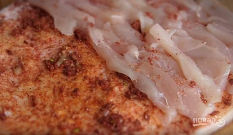 4. Куриное филе нарежьте тонкими полосками. Выложите его на одну половину сала, посыпьте смесью специй.
