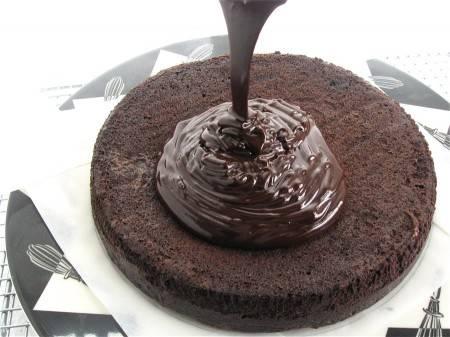 5. Остудите корж и выложите на большую тарелку. Шоколад выложите в сотейник, добавьте сливки, поставьте на огонь и мешайте, пока не пойдет пар и не растворится шоколад. Затем снимите с огня. Шоколадным кремом залейте корж.