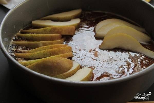 4. Вымойте, обсушите и нарежьте тонкими дольками груши. На дно жаропрочной формы выложите карамель и распределите ровным слоем фрукты. Выкладывайте грушу красиво по кругу.