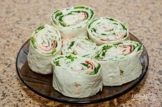 4.Разверните лаваш и смажьте его майонезом с чесноком, распределите начинку и посыпьте зеленью, заверните все в рулет и оберните пленкой. Отправьте в холодильник на полчаса, затем нарежьте кусочками и подавайте.