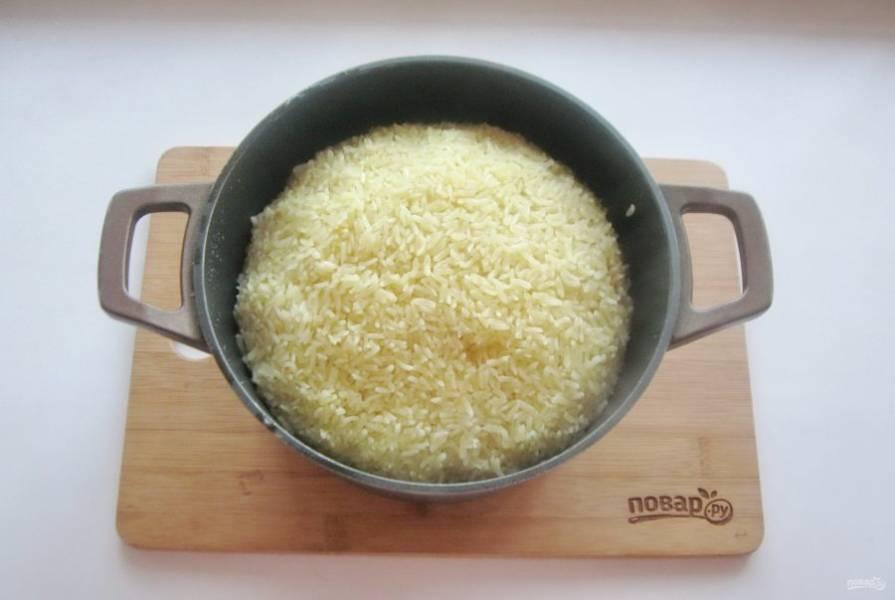 После соберите рис горкой к середине с боков. Накройте казан крышкой, огонь убавьте до минимума и варите плов еще 15-20 минут до готовности.