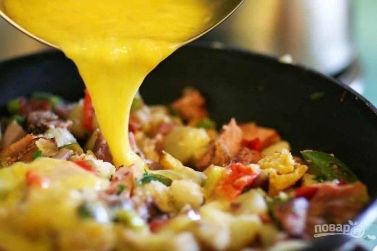 5.Разбейте в отдельную миску куриные яйца, посолите и поперчите, влейте в сковороду.