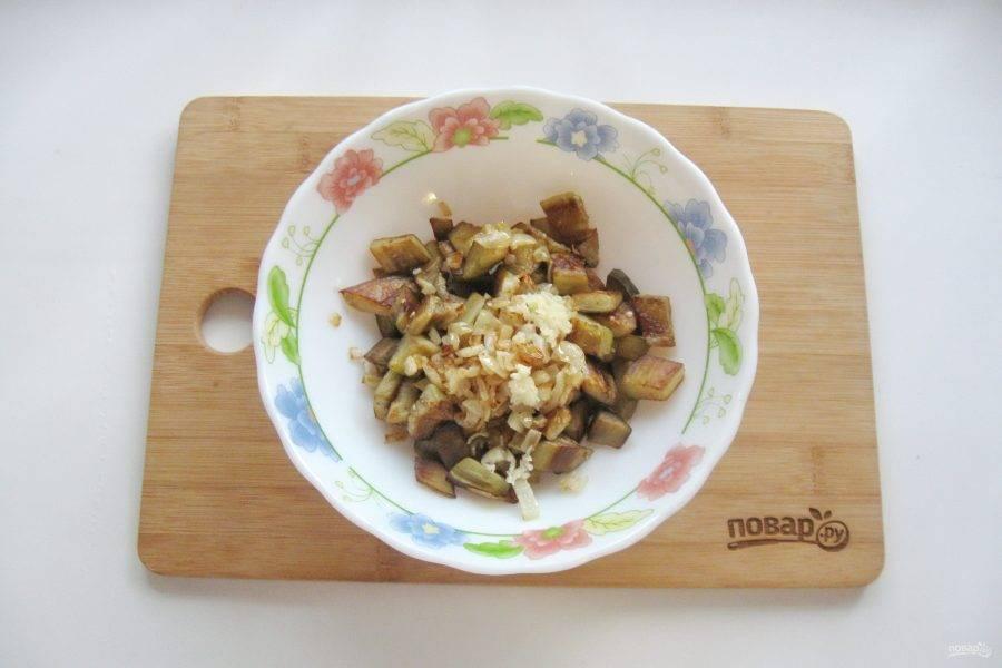 Чеснок измельчите любым способом и выложите в салатник с баклажанами и луком.