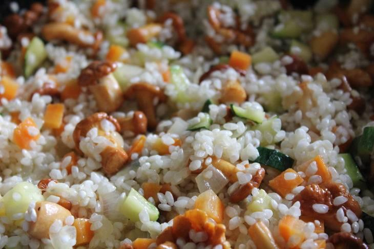 Обжариваем лук на разогретой маслом сковородке. Постепенно добавляем морковь, грибы, цукини, перец, чеснок, рис. Перемешиваем.