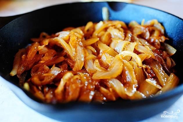 Сначала поджарим лук. Возьмите 50 грамм сливочного масла, растопите на сковороде и выложите лук, нарезанные кольцами. Тушите его на среднем огне 20 минут. Лук должен выпустить свой сок и потушиться немного в нём.