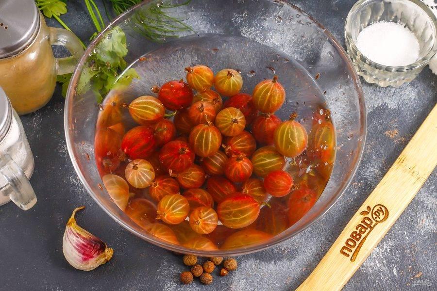 Крыжовник промойте в воде, обрежьте хвостики с ягод.