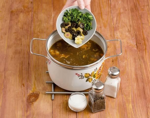 13. Наша грибная солянка с лимоном в домашних условиях почти готова. Добавьте в кастрюлю зелень, чеснок и маслины с оливками. Попробуйте на соль и перец — и снимите кастрюлю с огня. Накройте крышкой, дайте настояться минут 20-25.