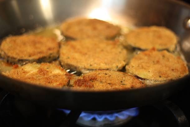 2. В небольшой мисочке взбить яйца. Отдельно высыпать муку и панировочные сухари. Кружочек баклажана опустить в яйца, затем обвалять в муке, потом снова в яйца и в панировочные сухари (это сделает жареные баклажаны с сыром в домашних условиях невероятно хрустящими). На сковороде разогреть растительное масло и выложить туда баклажаны. Обжарить с двух сторон до румяной корочки на сильном огне.