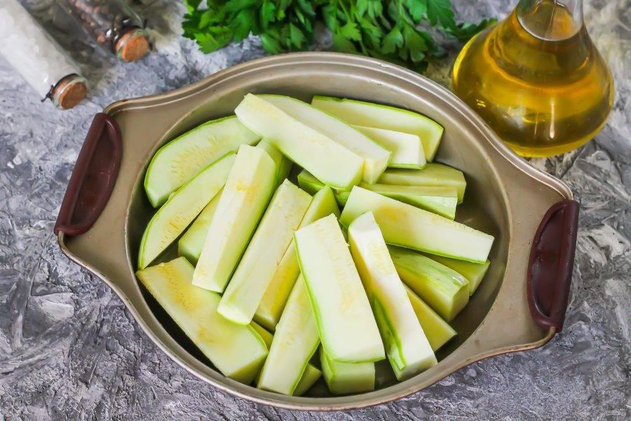 Кабачки промойте в воде, срежьте хвостики с обеих сторон овощей и нарежьте их крупными брусочками. Смажьте форму для запекания растительным маслом, лучше всего - оливковым холодного отжима. Выложите в форму кабачковую нарезку.