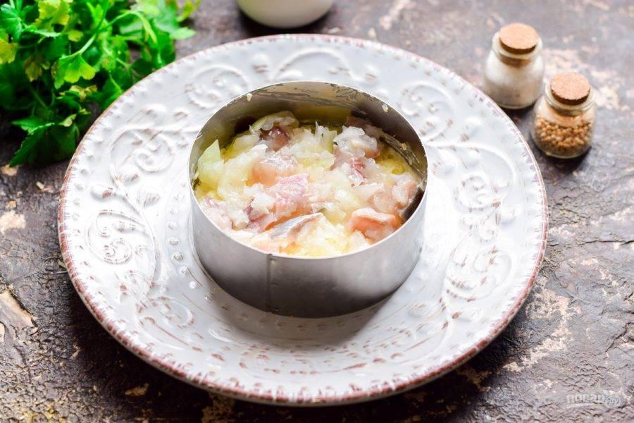 Выложите первым слоем картофель, поверх немного сельди и лука.