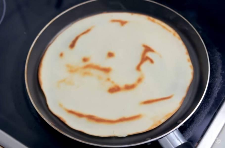 3. Холодную сковороду смажьте растопленным сливочным маслом и с помощью ложки распределите на ней тесто тонким слоем. Жарьте до золотистого цвета с обеих сторон на небольшом огне.