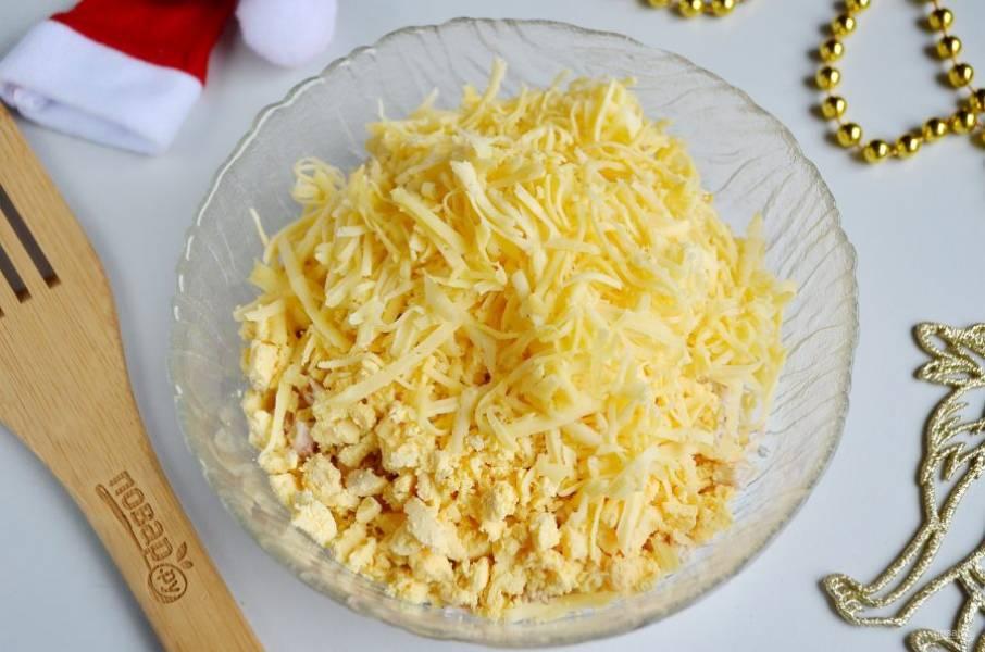 Отделите желтки от белков. Белками будем декорировать салат, а желтки порежьте кубиками и добавьте к филе. Туда же — тертый сыр.