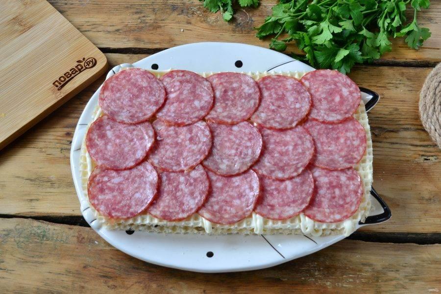 Затем положите второй вафельный лист, покройте его майонезом и выложите на него тонкие ломтики колбасы.