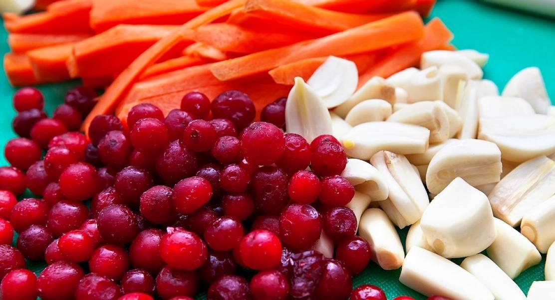 На следующий день подготовьте овощи и ягоды, которыми будем шпиговать окорок. Чеснок можете порезать (каждый зубчик — на половину), клюкву промойте, а морковку порежьте соломкой.