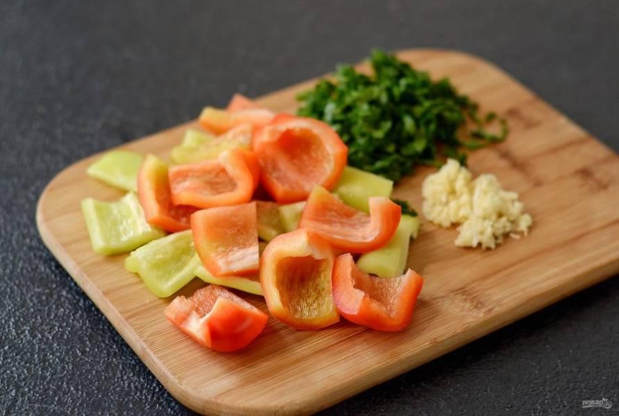 Перец помойте, очистите от семян, удалите хвостик. Нарежьте крупными ломтиками. Чеснок пропустите через пресс, зелень мелко порубите.
