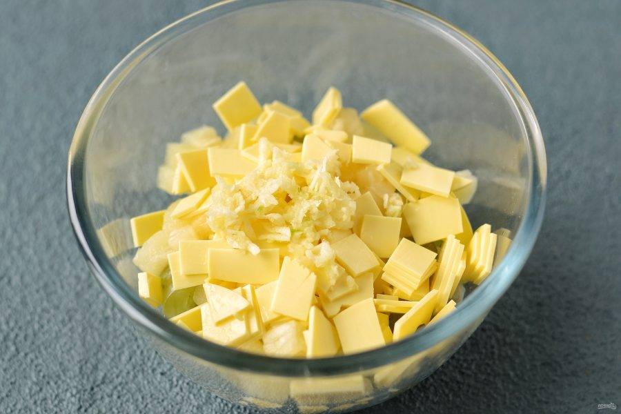 Сыр нарежьте кубиками. Чеснок измельчите через пресс.