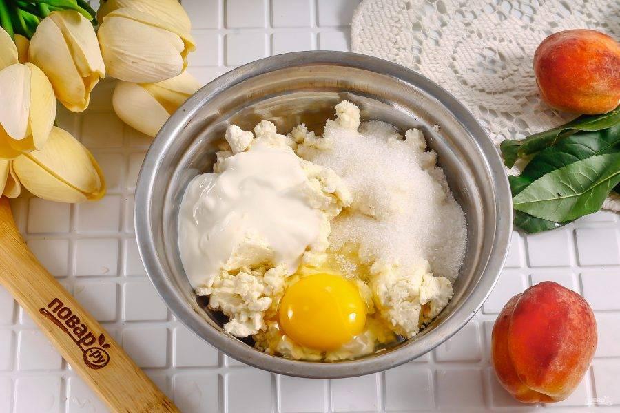 Тем временем перетрите в глубокой емкости рикотту, сахар, соль. Вбейте туда же куриное яйцо и выложите сметану любой жирности. Тщательно перемешайте.