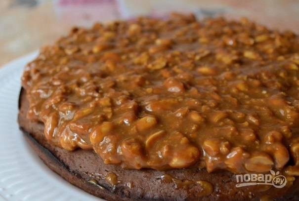 9. Выложите на тарелку корж и при желании пропитайте его сладким сиропом, кофе или алкоголем, например. Ровным слоем распределите ореховую массу.