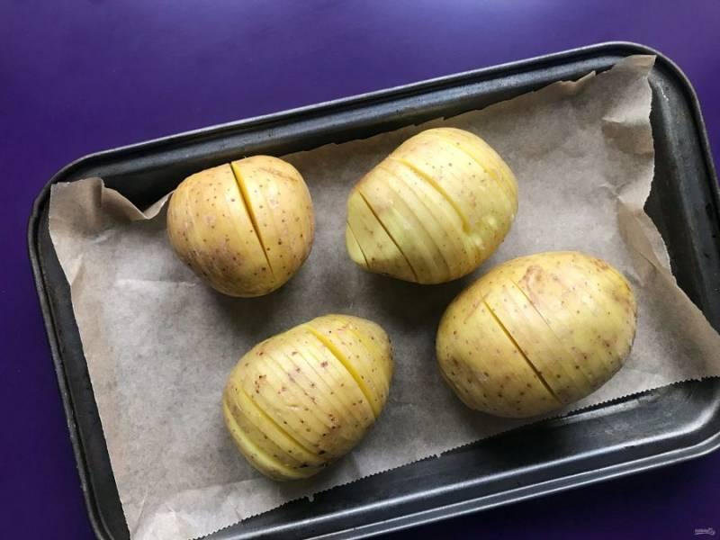 Картофель в кожуре хорошо помойте щеточкой, обсушите. Нарежьте на тонкие ломтики, но не до конца. Дно картошки должно остаться целым.